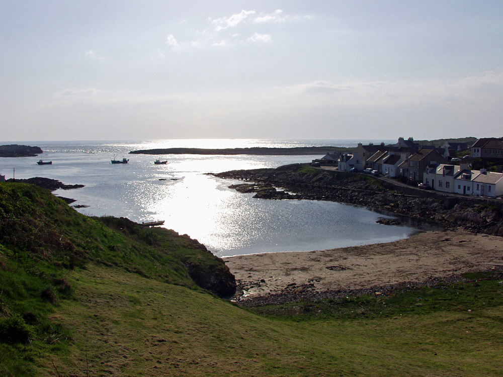 Picture of a view over a small bay with a village on the shore in bright sunshine
