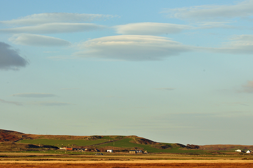 Picture of lenticular clouds over a farm below low hills