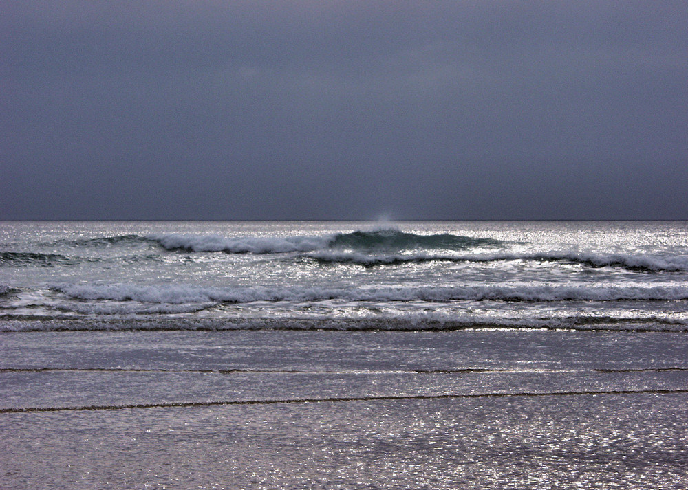 Picture of waves breaking as they reach a beach, lit up in sunlight under a dark sky