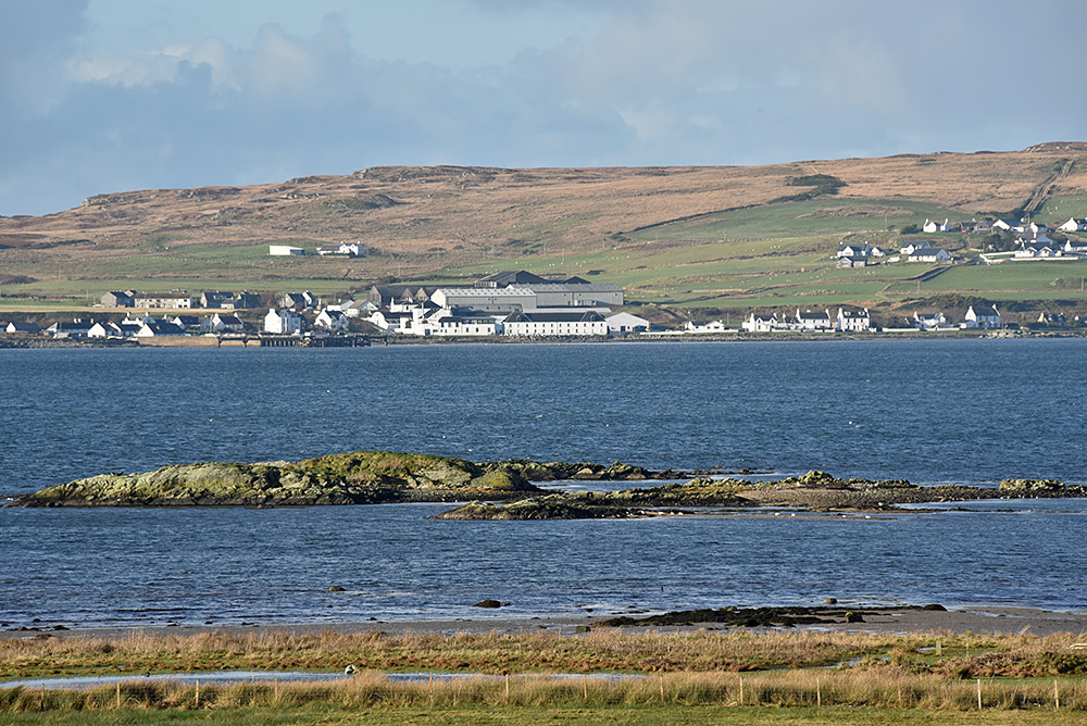 Picture of a village with a distillery seen across a sea loch