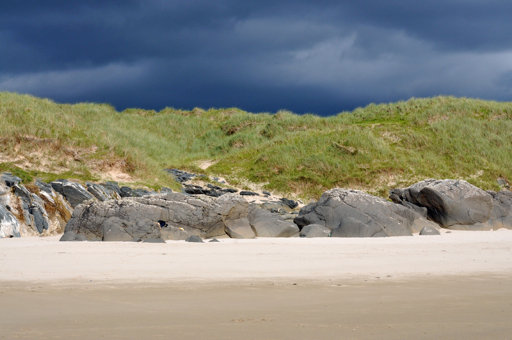 Picture of black clouds above dunes bathed in sunshine