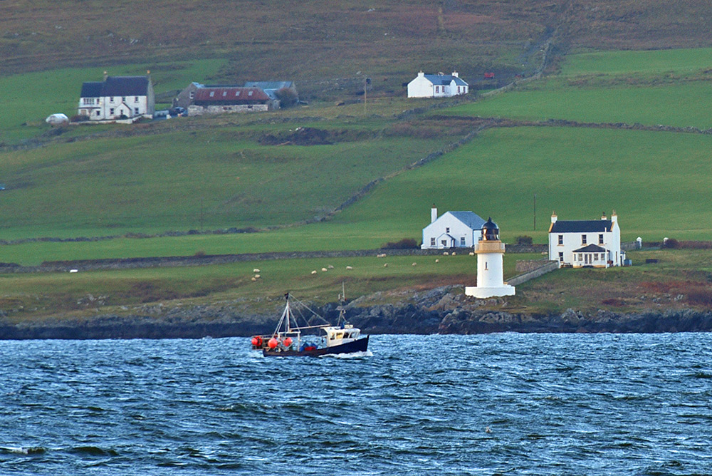 Picture of a fishing boat passing a small lighthouse in a sea loch