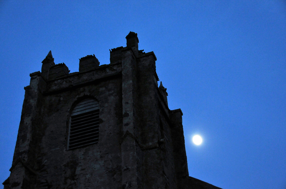 Picture of a church tower with the Moon behind in the haze