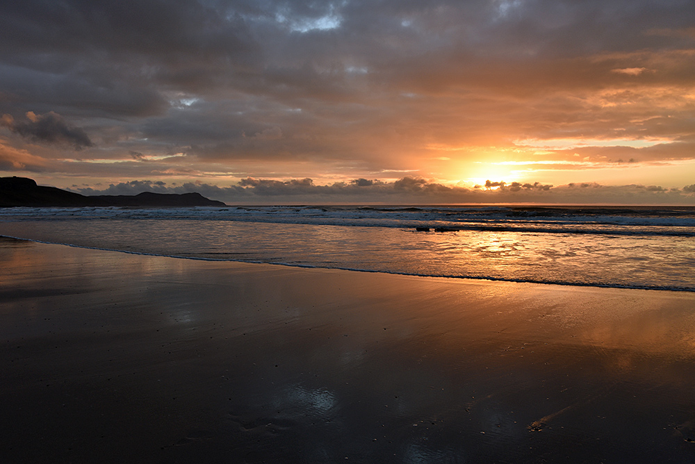 Picture of a cloudy November sunset in a bay with a sandy beach