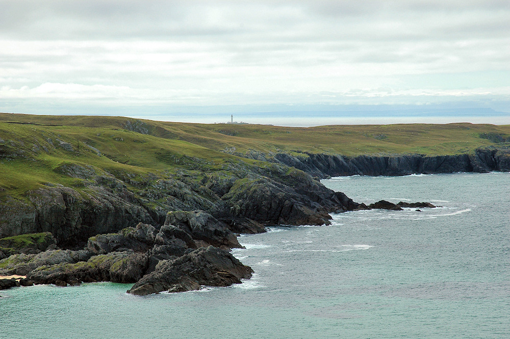 Picture of a lighthouse in the distance behind a bay and steep cliffs