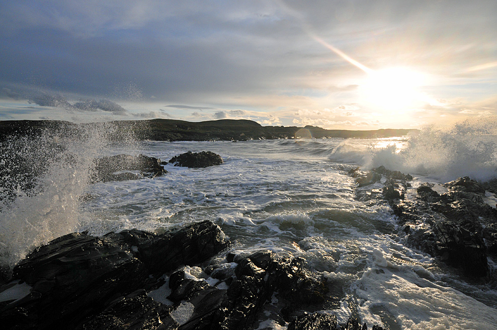 Picture of waves breaking over rocks in front of a low sun