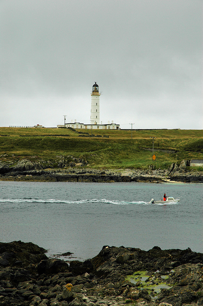 Picture of a lighthouse on an offshore island, a boat passing through the channel