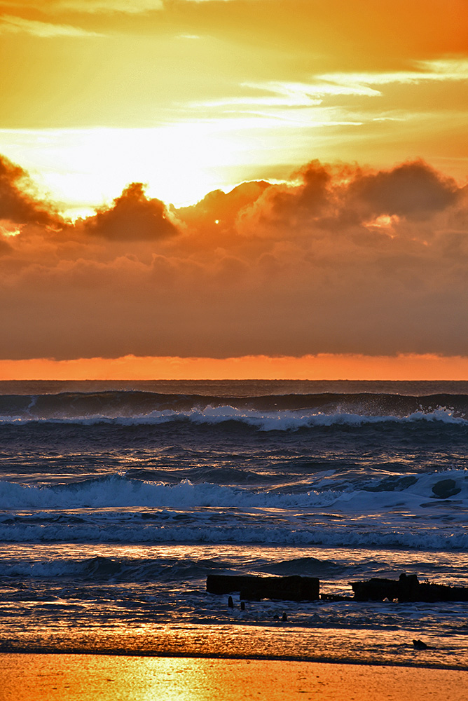 Picture of a beach and waves bathed in orange light as sunset approaches