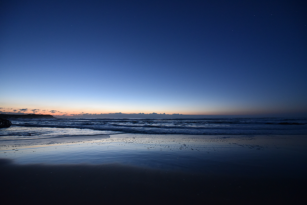 Picture of dusk over a bay with a sandy beach