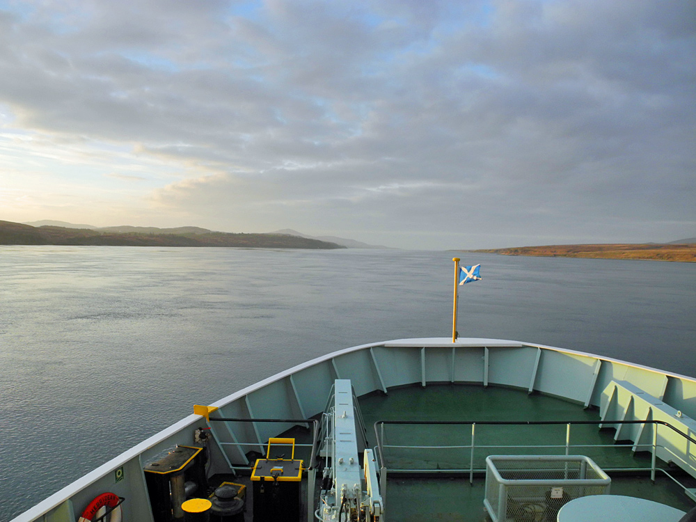 Picture of a view from a ferry travelling through a sound between two islands in the evening