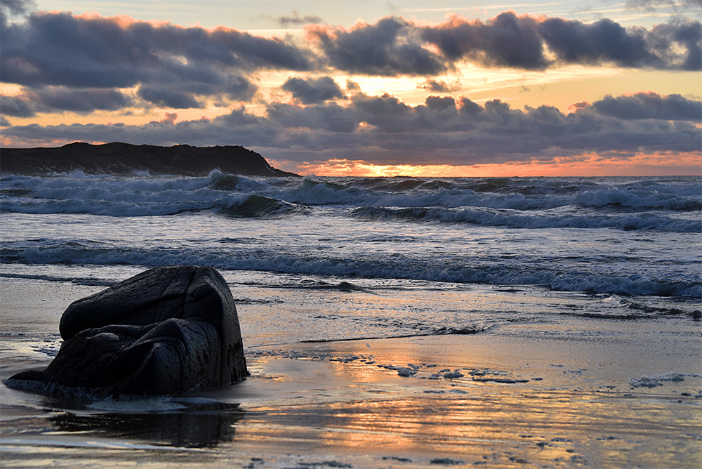 Picture of a moody late afternoon on a beach approaching a cloudy sunset. A large boulder on the beach