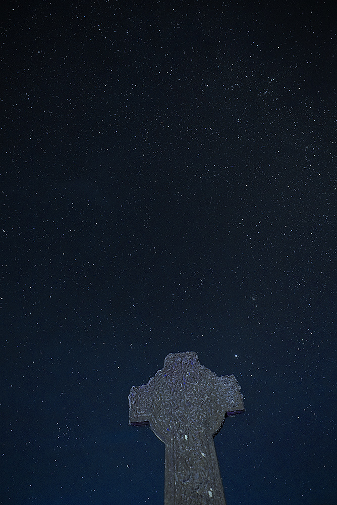 Picture of a Celtic cross under a night sky with thousands of stars