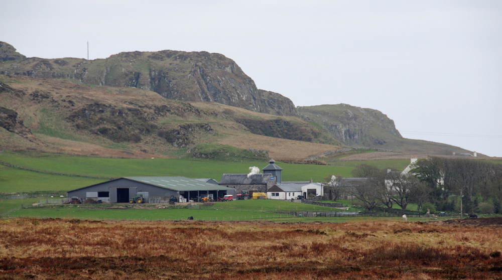 Picture of a farm and a distillery below some crags