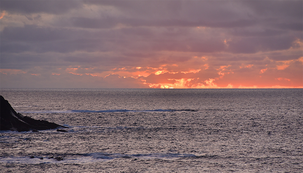 Picture of the last seconds of a cloudy sunset, just a tiny sliver of the sun still visible