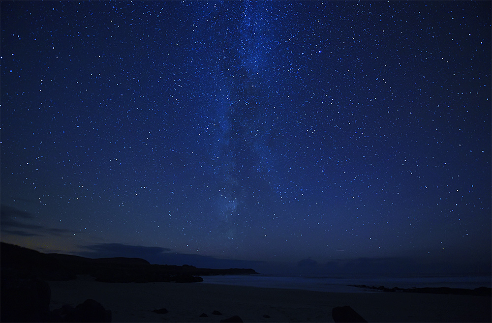 Picture of the Milky Way in the night sky over a bay with a beach