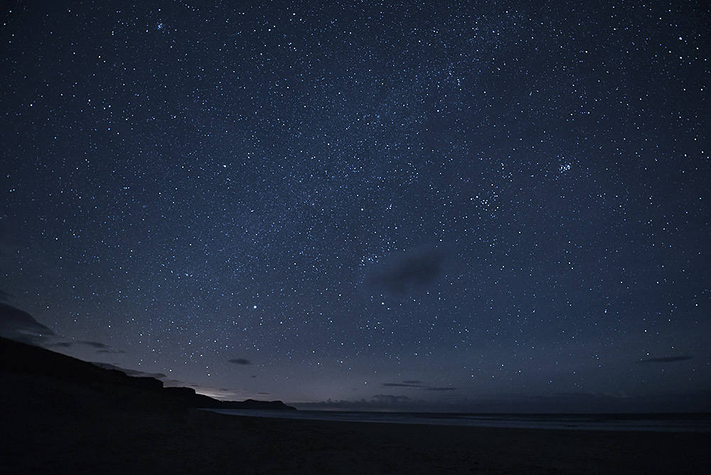 Picture of the night sky with thousands of stars over a wide bay