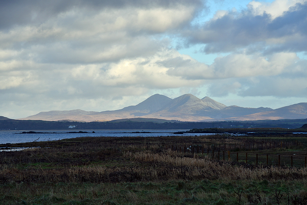 Picture of three mountains seen from the shore of a sea loch