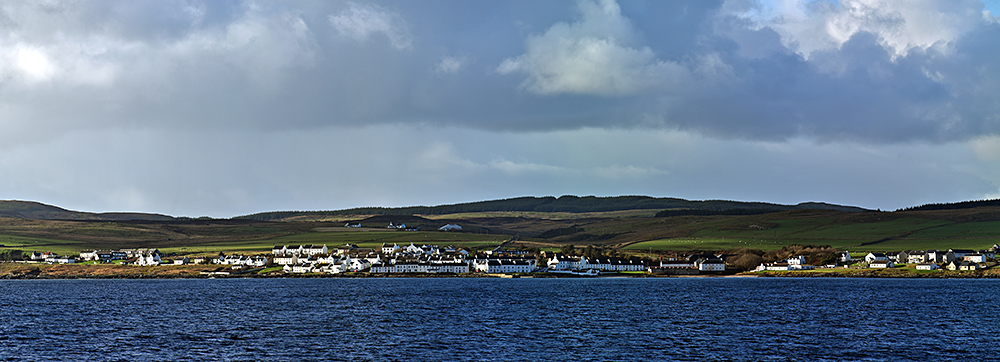 Panoramic picture of a coastal village seen across a sea loch