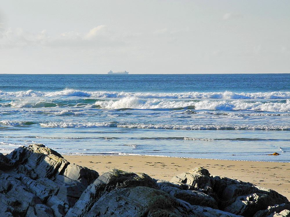 Picture of a larger tanker ship passing a beach