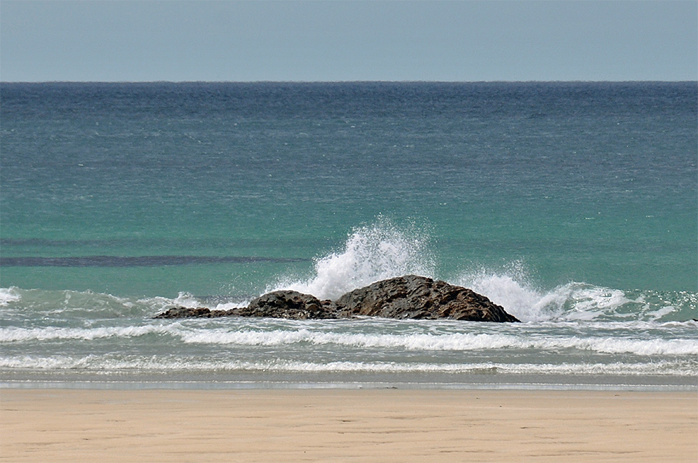 Picture of a small wave splashing over small rocks on a beach