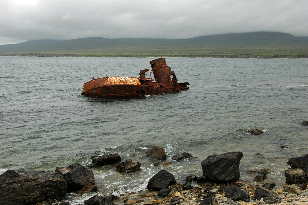 Picture of a shipwreck in a sound between two islands on a cloudy day
