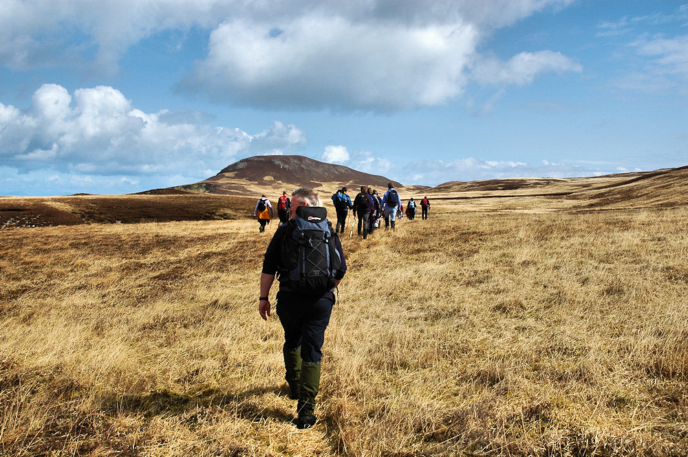 Picture of a group of walkers approaching a hill over rough ground
