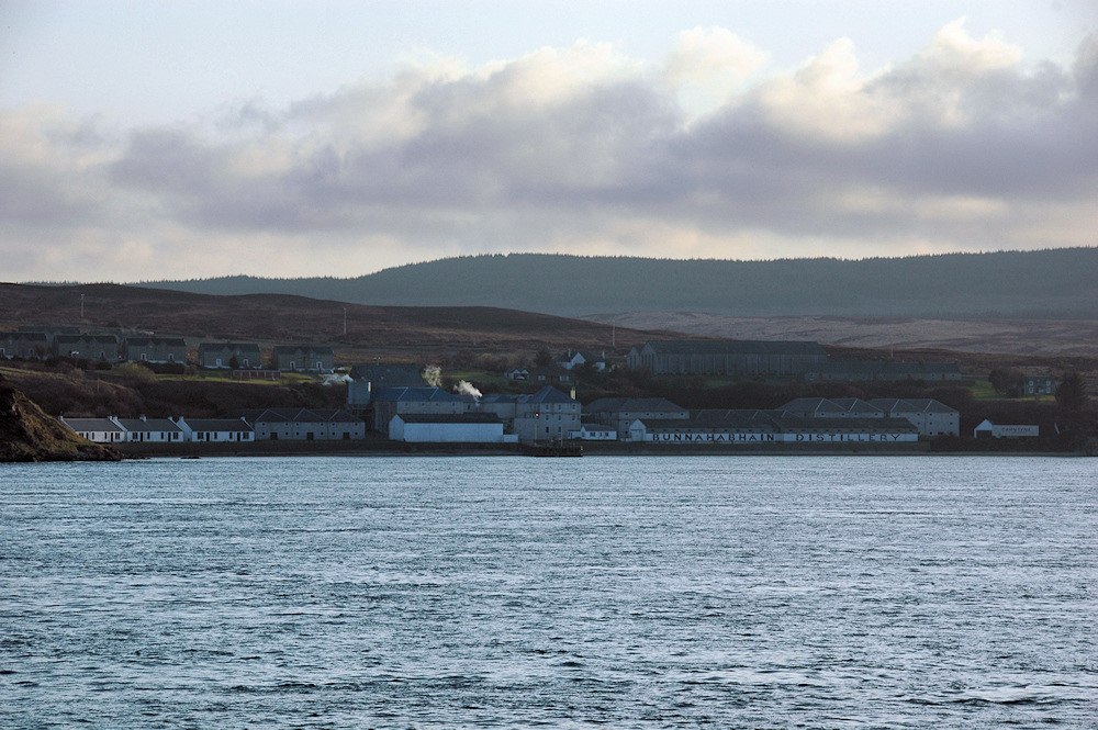 Picture of a coastal distillery in the evening light, seen from a passing ferry