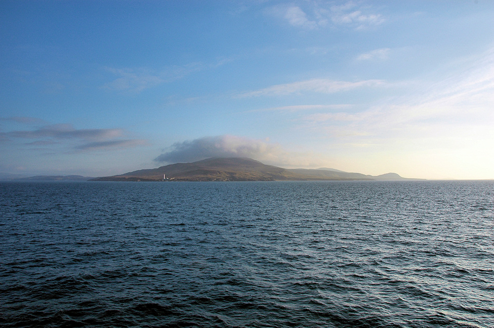Picture of a view from a ferry to an island, clouds over a mountain on the island