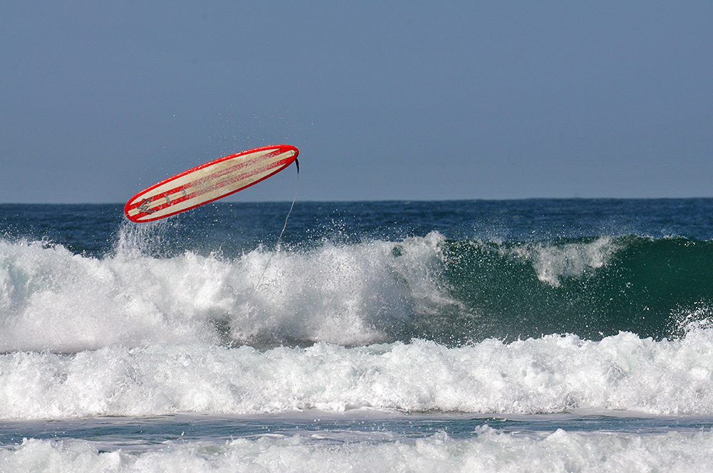 Picture of a surfboard in the air after the surfer fell off in the waves