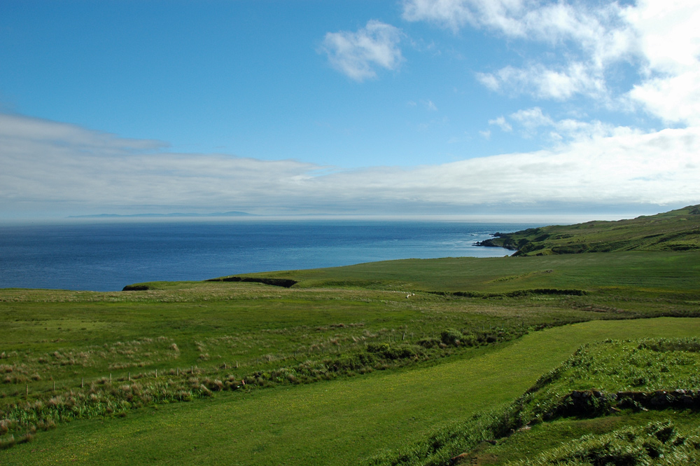 Picture of a view across a green coast over the sea to another island