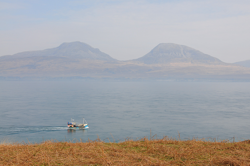 Picture of a view over a sound between two islands, a fishing boat passing