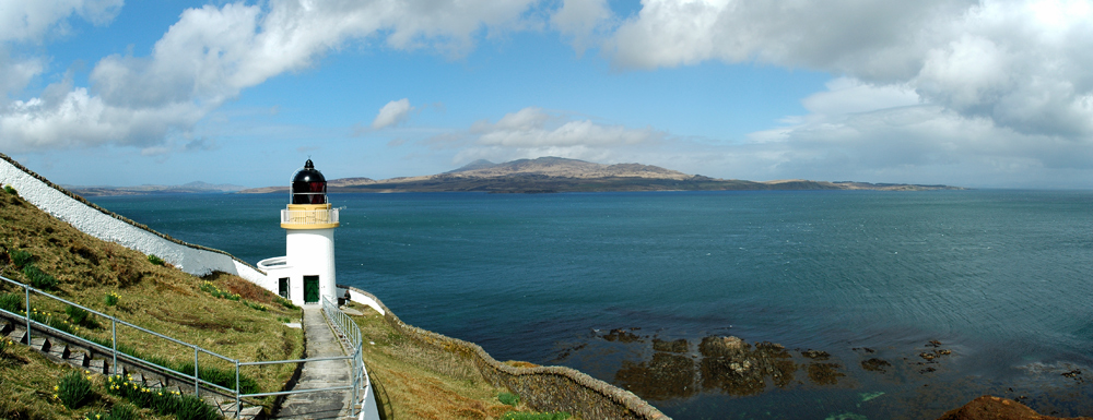 Panoramic picture of a view over a sound between two islands from the grounds of a small lighthouse