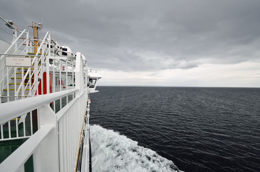 Picture of a view from the upper deck of a modern ferry cruising on a cloudy day