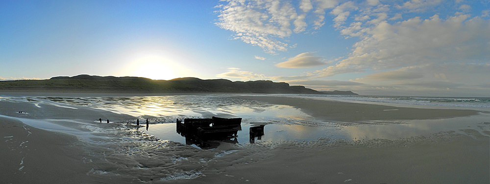 Panoramic picture of a November sunrise over a bay with a sandy beach and a wreck