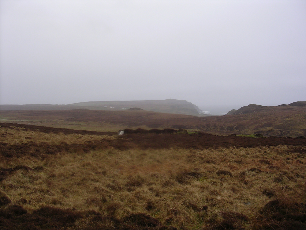 Picture of a hilly landscape with tussocks in the rain, a monument in the distance