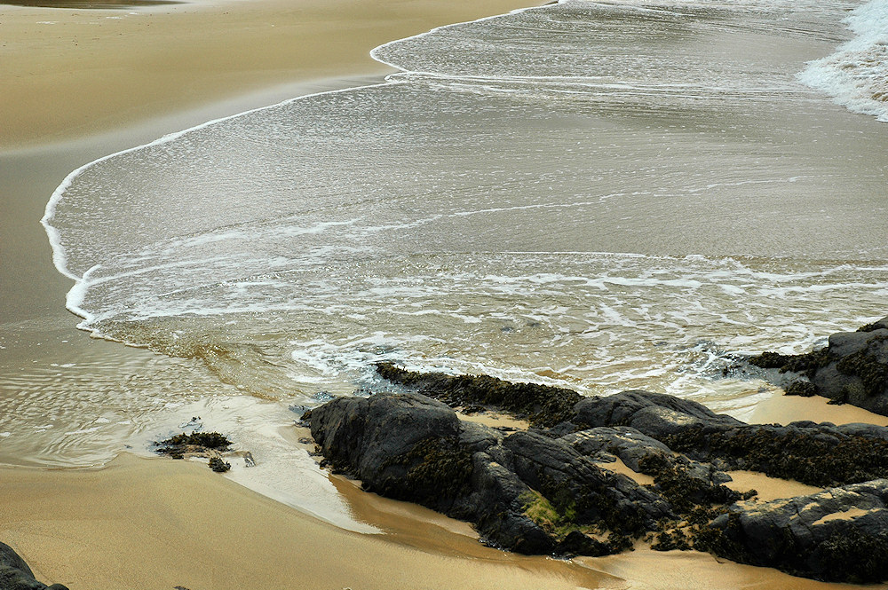 Picture of waves swirling on a beach after breaking