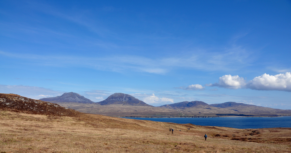 Panoramic picture of a group of walkers approaching a sound between two islands on a sunny day