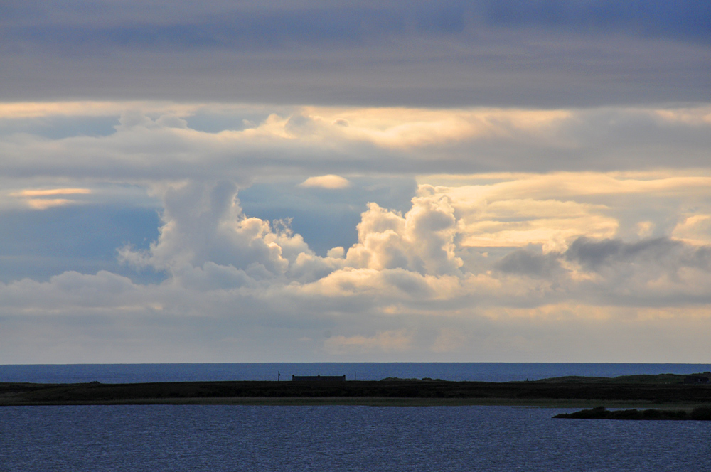 Picture of a coastal cottage below some dramatic clouds