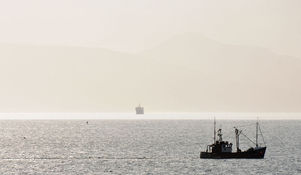 Picture of an approaching ferry through haze, a fishing boat in the foreground