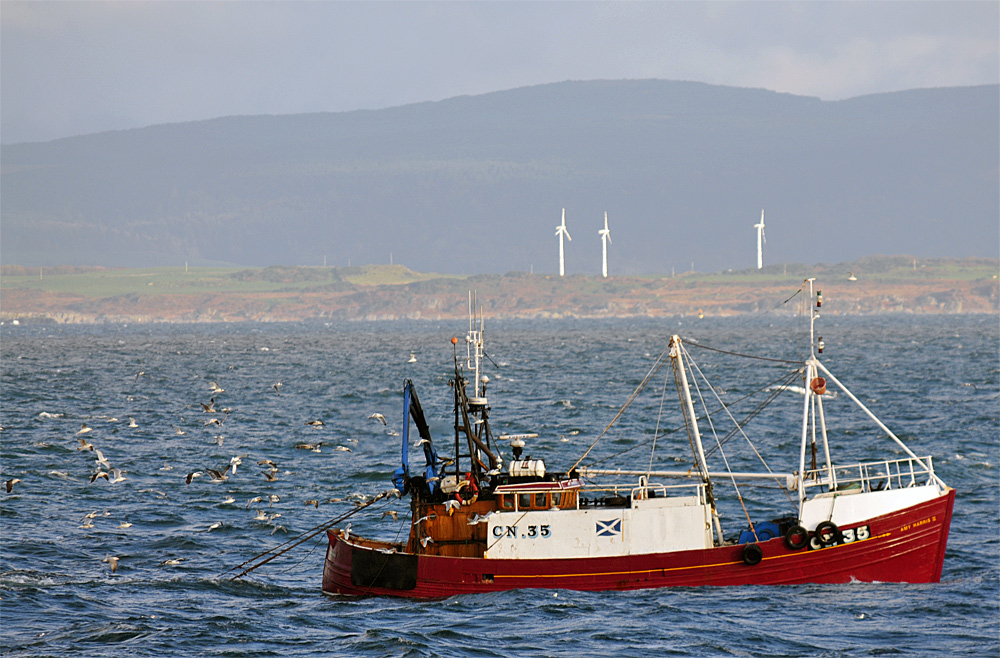 Picture of a fishing boat at work, an island with three wind turbines in the background