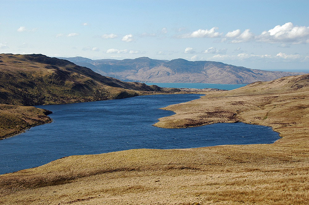 Picture of a hill loch with a sound between two islands in the background