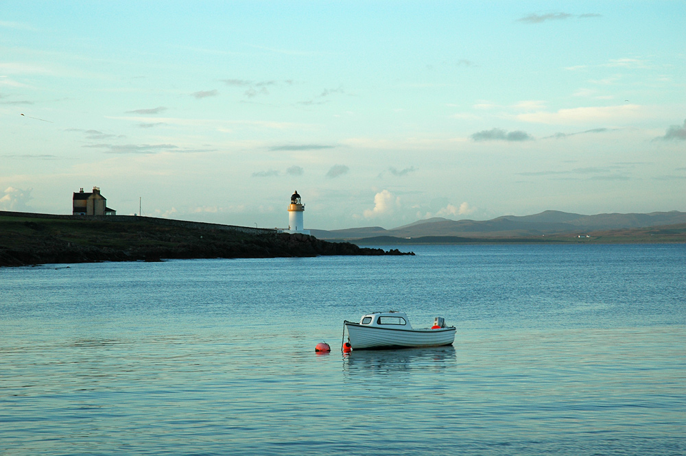 Picture of a small lighthouse on a sea loch shore, a small boat moored offshore