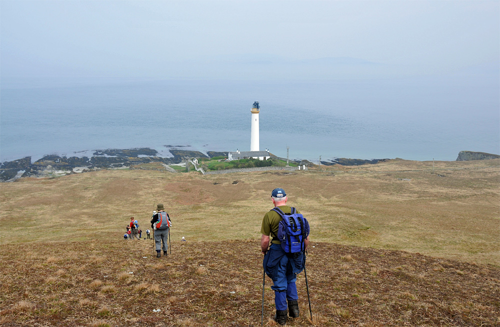 Picture of a group of walkers approaching a lighthouse at the bottom of a hill