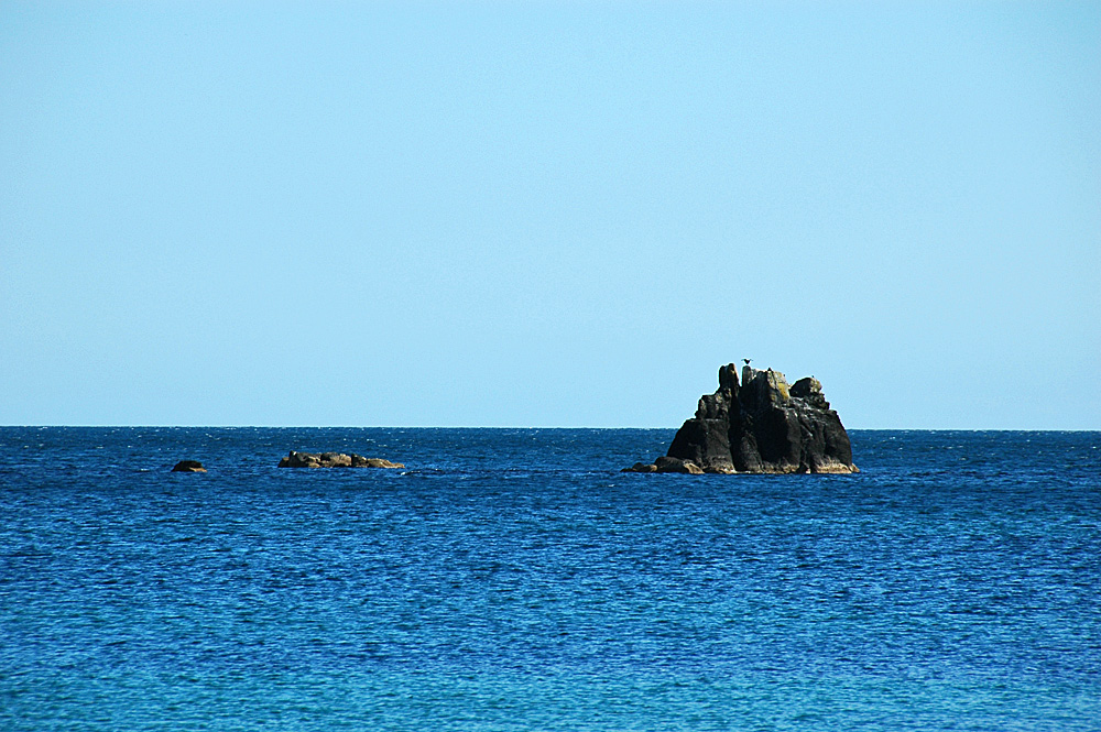 Picture of a few offshore rocks in a blue sea