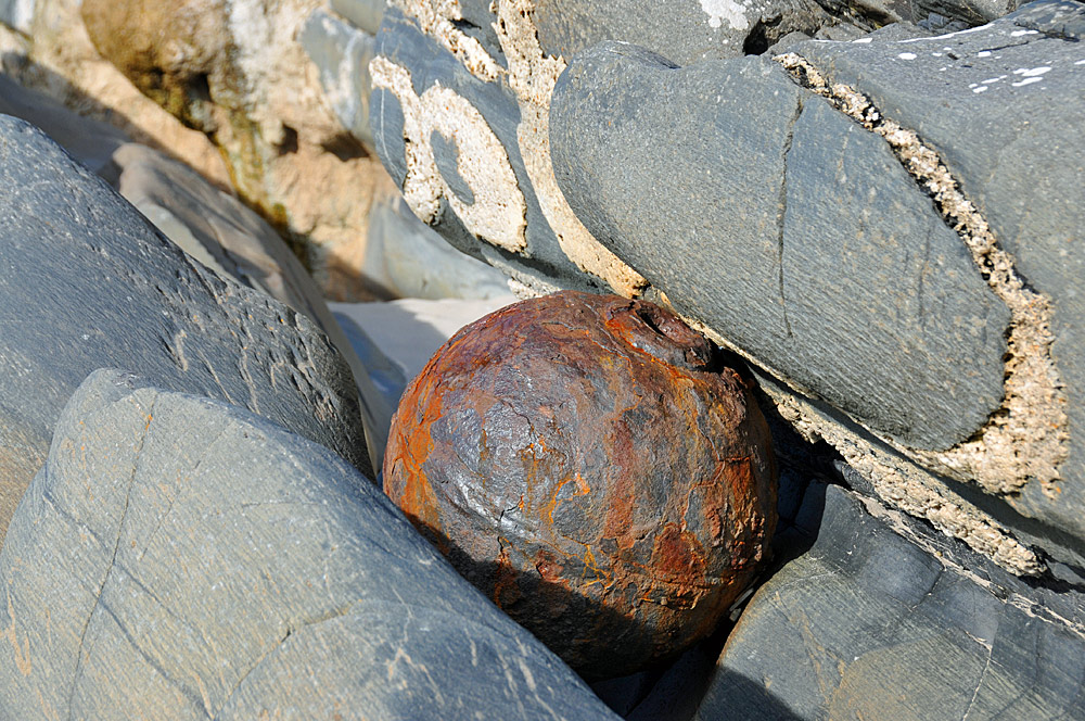 Picture of a rusty metal ball wedged between rocks on a beach