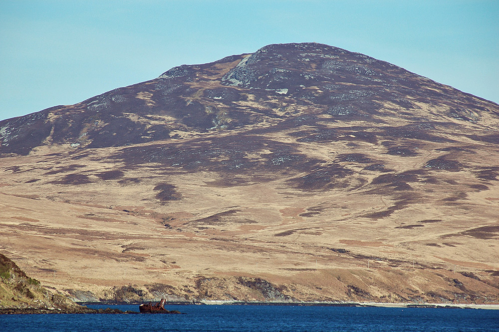 Picture of a hill over a sound, a wreck on the shore of the sound