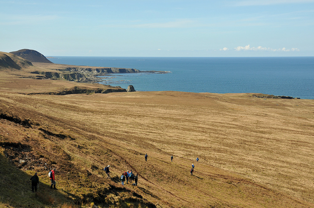 Picture of a group of walkers descending on to a raised beach