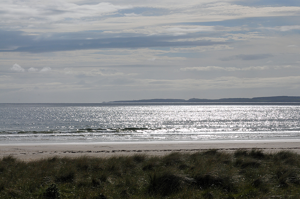 Picture of a view over a beach out to see and another part of an island in the distance