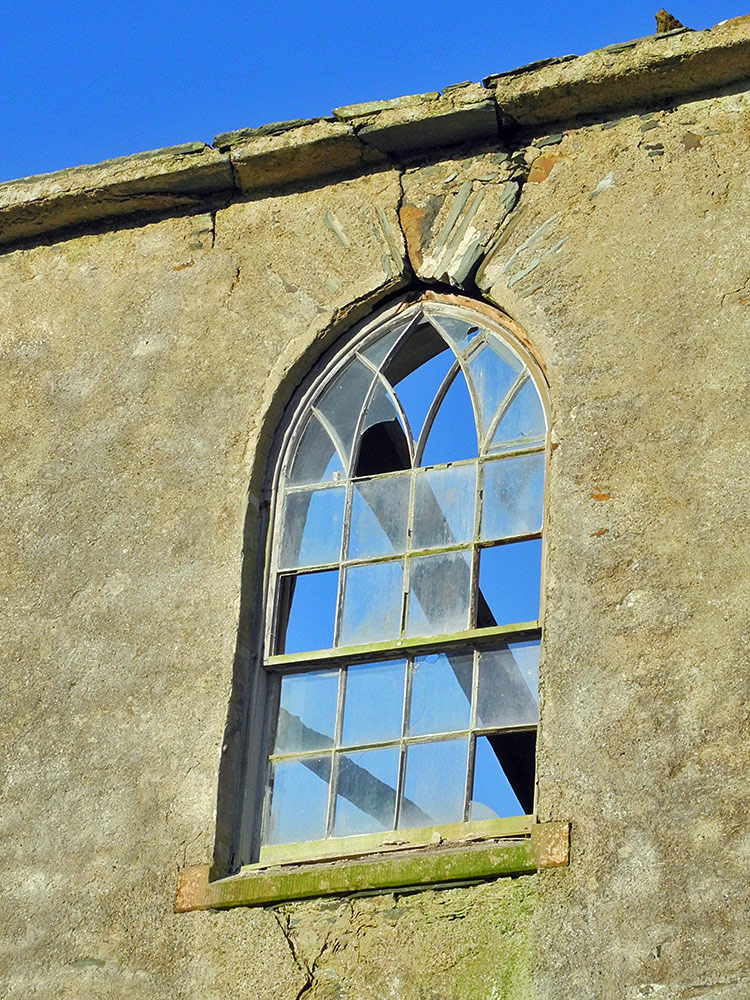 Picture of a broken window in the ruin of an old church