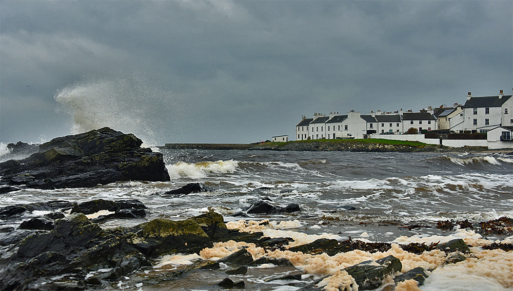 Picture of a grey and blustery day on the shore next to a coastal village
